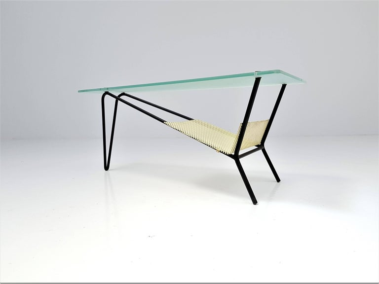An end table by Robert Mathieu, France, circa 1955  An end table by Robert Mathieu, circa 1955. Consisting of a lacquered black tubular structure, a sandblasted glass top, brass fixings and a perforated tray.   Robert Mathieu is recognised as an