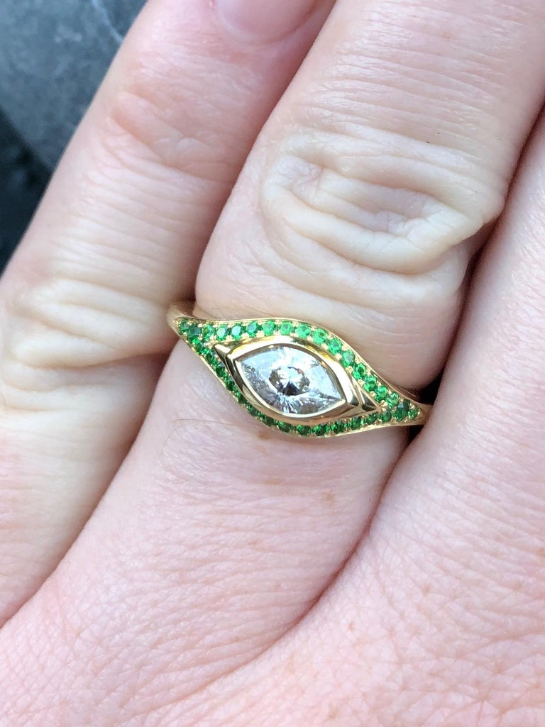 A singular Cleopatra's eye cut diamond (E/VS- 0.64 ct) with a tsavorite pavé. An engagement truly like no other, this diamond is absolutely fascinating.  Hand carved wax/cast, made by hand start to finish by our master goldsmith.  Size 7.25 (can be