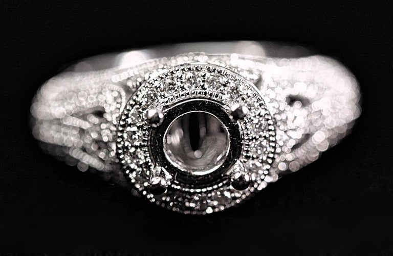 An open weave engagement ring with diamonds. The ring is 18K white gold with .72 carat total weight of round brilliant cut diamonds.  The center measures 6 1/2mm and would be beautiful with a diamond or colored stone put in the center. The mounting