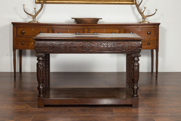 An English George III period oak console table from the early 19th century, with carved drawer and Ionic capitals. Created in England during the early years of the 19th century, this oak console table features a rectangular planked top sitting above