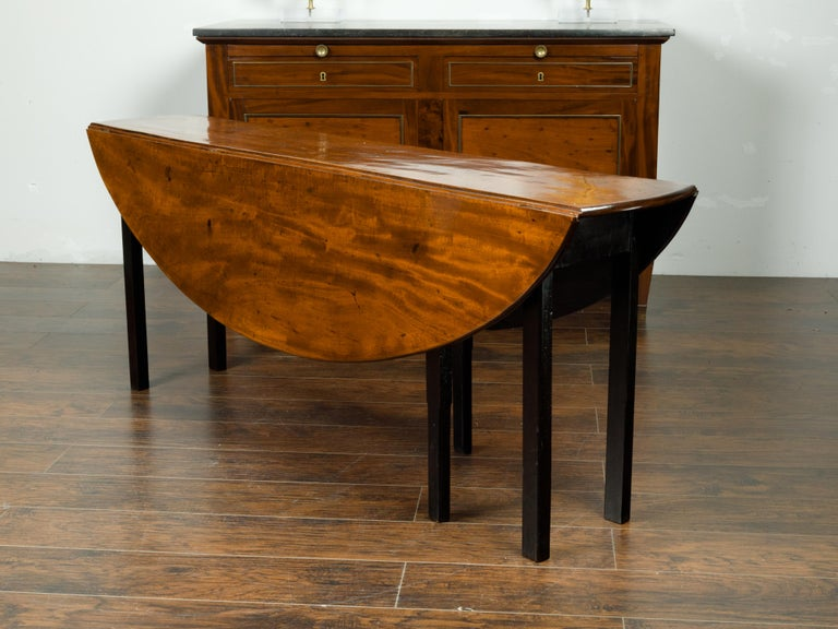 English 1820s Mahogany Drop Leaf Dining Table with Oval Top and Ebonized Legs For Sale 5