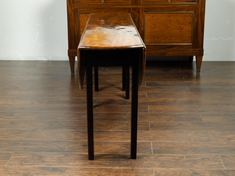 English 1820s Mahogany Drop Leaf Dining Table with Oval Top and Ebonized Legs For Sale 6