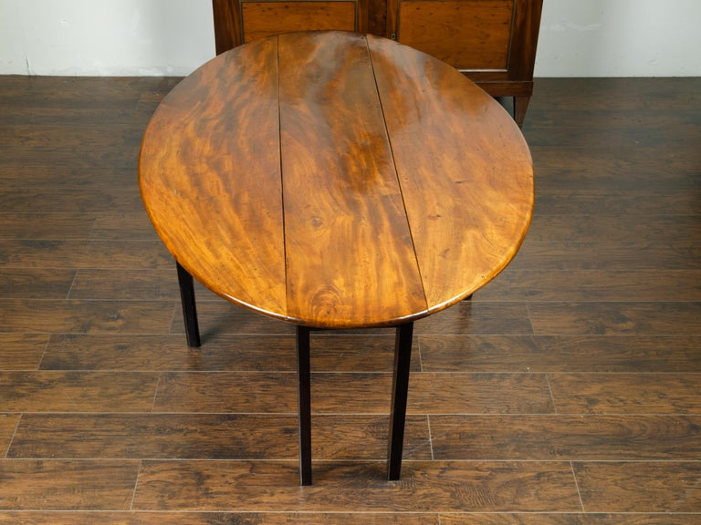 19th Century English 1820s Mahogany Drop Leaf Dining Table with Oval Top and Ebonized Legs For Sale