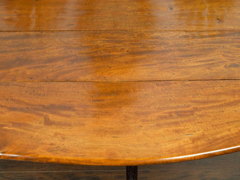 Wood English 1820s Mahogany Drop Leaf Dining Table with Oval Top and Ebonized Legs For Sale