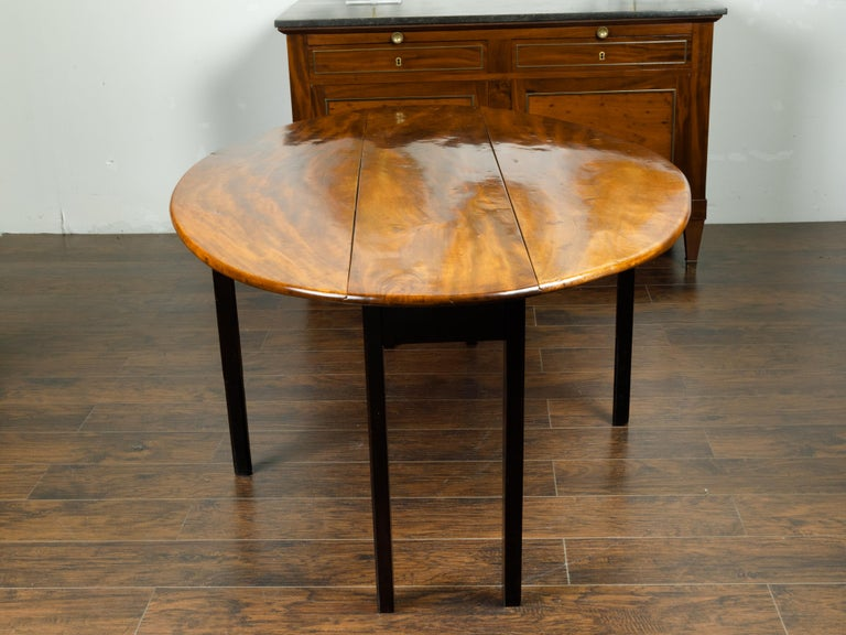 English 1820s Mahogany Drop Leaf Dining Table with Oval Top and Ebonized Legs For Sale 2