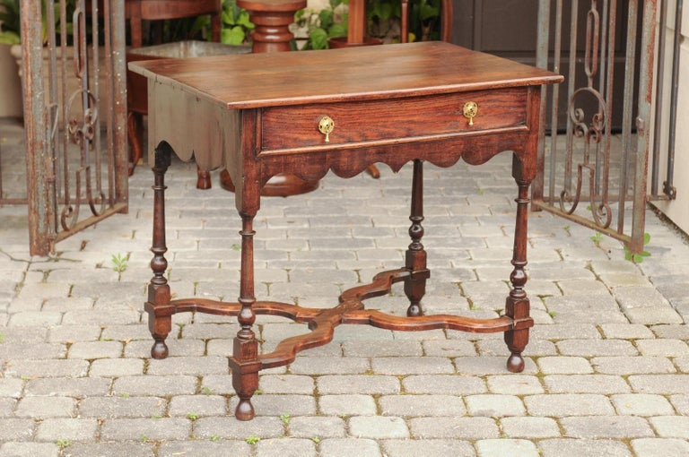 An English oak side table from the mid-19th century, with single drawer, turned legs and curving X-form cross-stretcher. Born in England during the second quarter of the 19th century, this exquisite side table features a rectangular top sitting