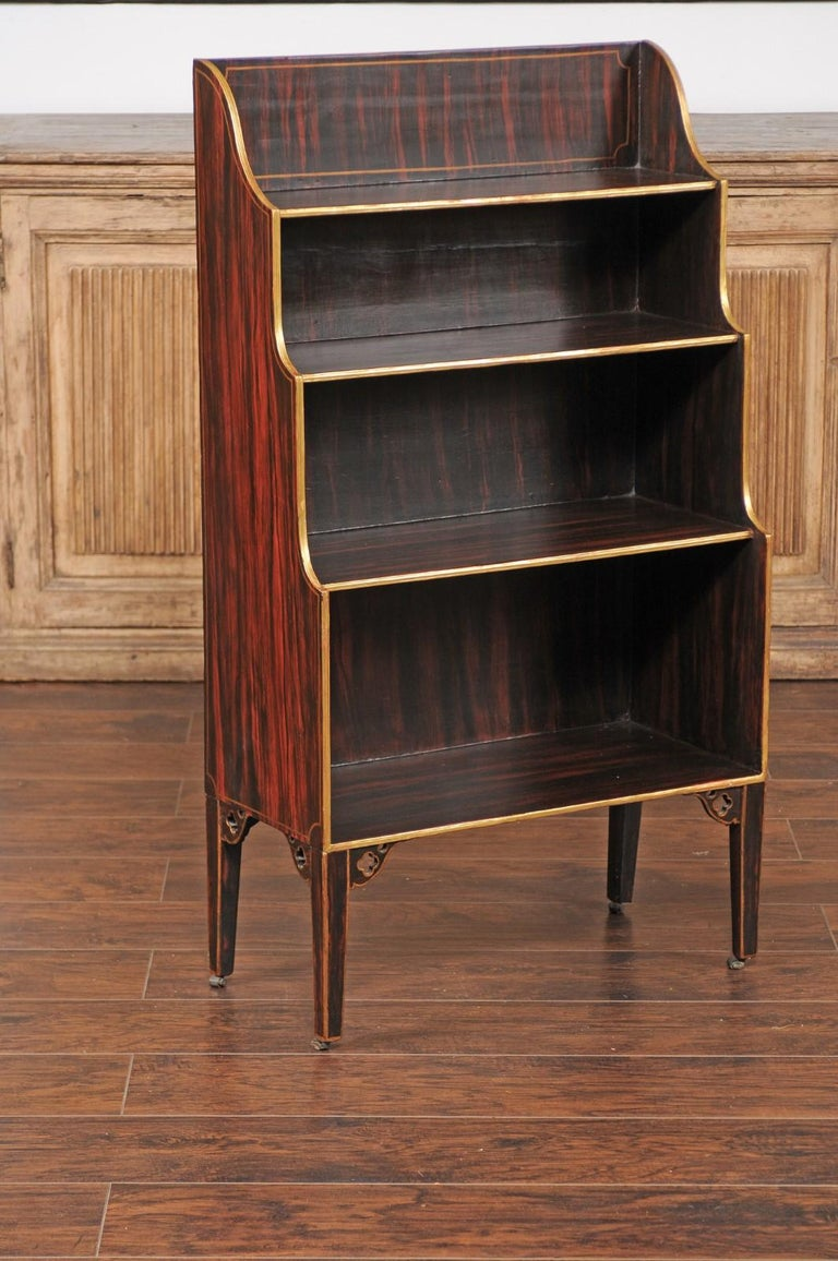 An English faux-painted waterfall bookcase from the mid-19th century, with gilded accents and tapered legs. Born in England during the 1850s, this waterfall bookcase features four open shelves of increasing size presenting a faux finish. The entire