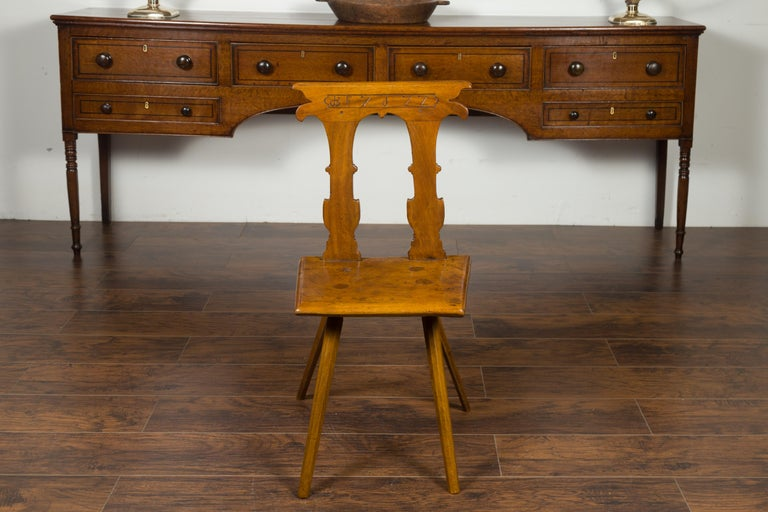 An English oak hall chair from the mid-19th century, with pierced back, carved letters and wooden seat. Created in England during the 1850s, this oak hall chair features a slightly slanted back, pierced in its center, carved on the sides and incised