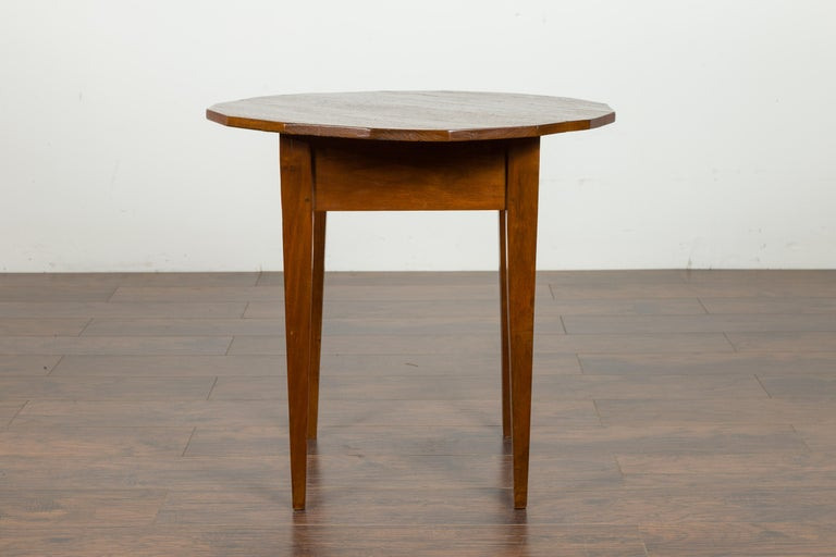 An English walnut side table from the mid-19th century, with polygonal top and tapered legs. Created in England during the third quarter of the 19th century, this side table features a polygonal top resting above a square-shaped apron. The table is