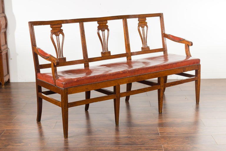 An English walnut three-seat bench from the mid-19th century, with leather seat and carved back. Created in England during the third quarter of the 19th century, this walnut bench features a pierced back adorned with delicate volutes on the splats,
