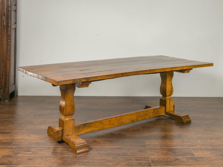 An English elm and walnut farm table from the late 19th century, with trestle base. Born in England during the third quarter of the 19th century, this farm table features a rectangular planked top sitting above a trestle base showcasing baluster