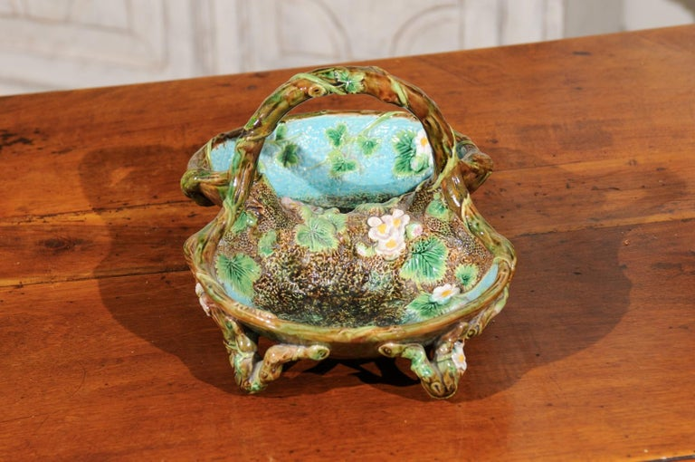An English mottled brown, green and turquoise Majolica strawberry basket from the late 19th century, signed George Jones. Born in England during the second half of the 19th century, this exquisite Majolica piece features a lovely palette made of