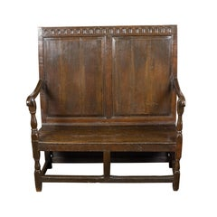 English 1870s Oak Bench with Carved Frieze, Scrolling Arms and Turned Legs