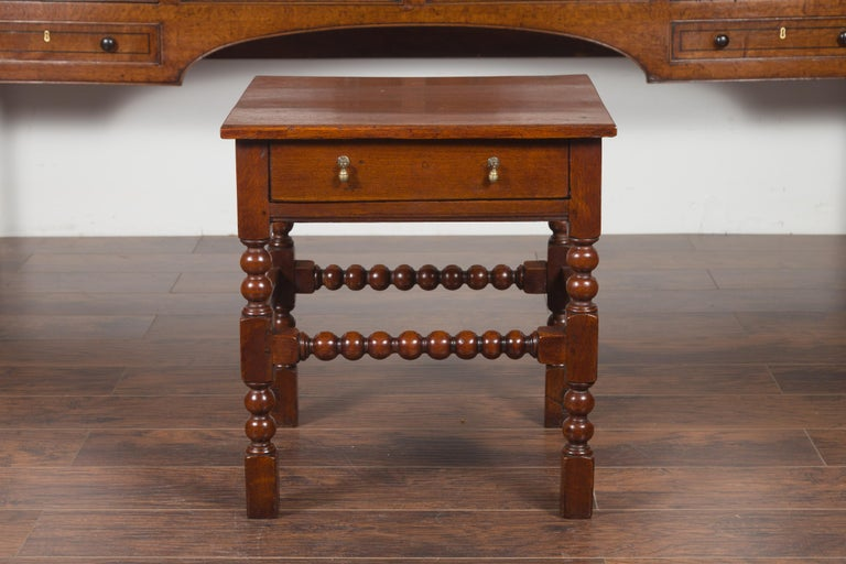 An English oak bobbin legs side table from the late 19th century, with single drawer and stretchers. Created in England during the third quarter of the 19th century, this oak side table features a rectangular top sitting above a single drawer,