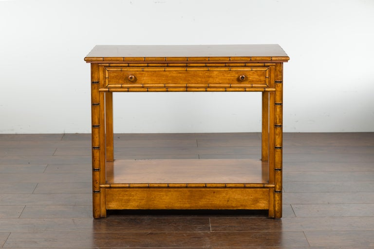 An English burl walnut faux bamboo table from the late 19th century, with ebonized accents, single drawer, lower shelf and petite hidden wheels. Created in England during the last quarter of the 19th century, this faux bamboo table features a