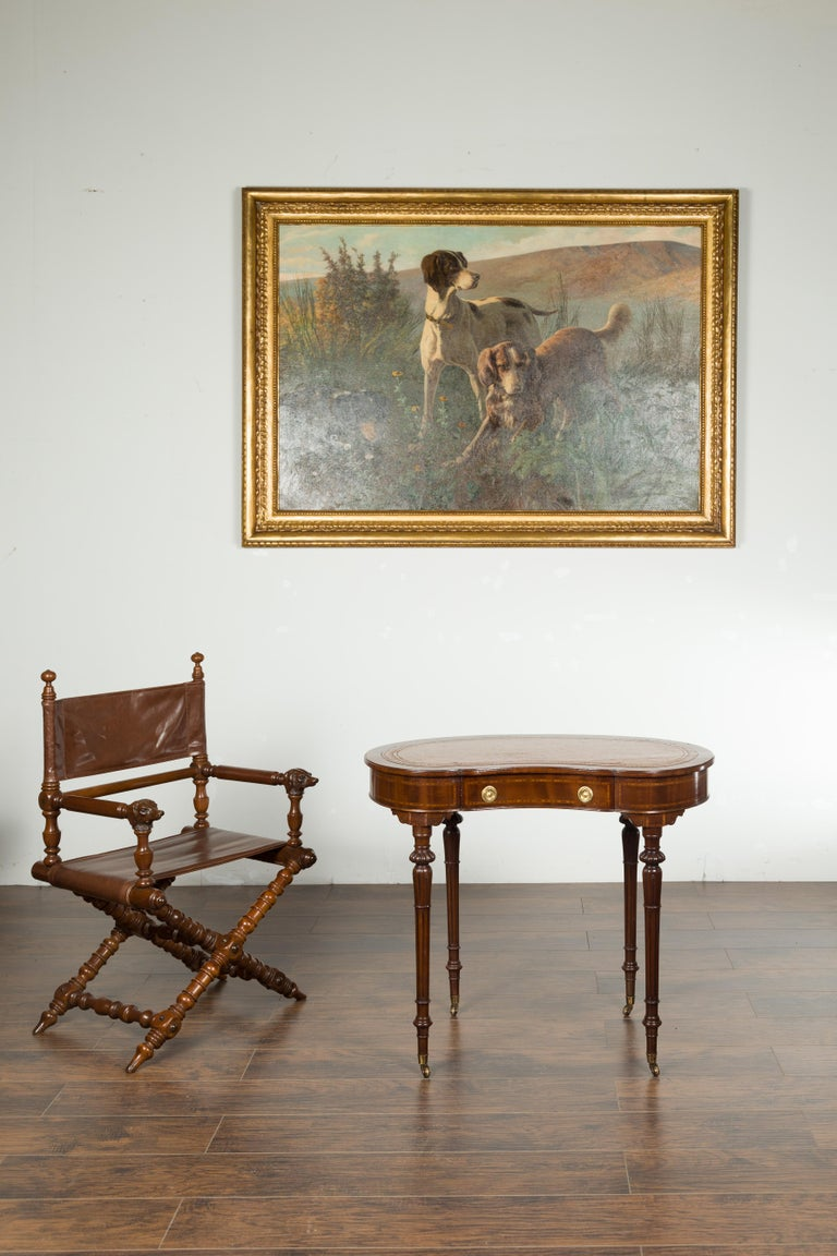 An English mahogany kidney table from the late 19th century, with leather top, banding and casters. Created in England during the last quarter of the 19th century, this mahogany kidney table features a shaped leather top sitting above a single