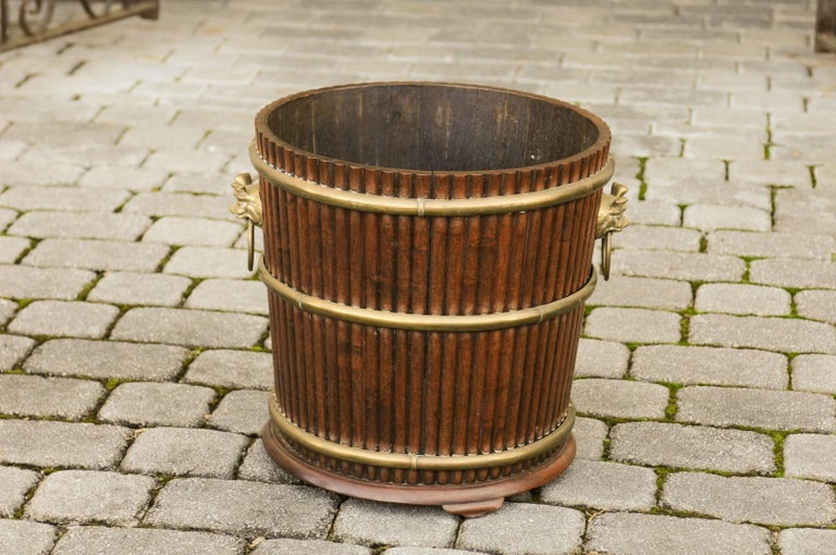 An English wooden bucket from the late 19th century, with reeded accents and brass motifs. Born in England during the later years of the 19th century, this charming bucket will charm you with its versatile aspect. Whether used as a planter, cachepot
