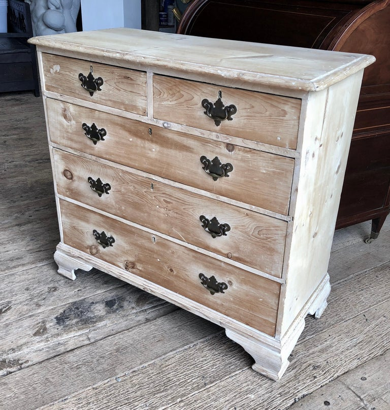 A late 18th century English chest of drawers in stripped and bleached pine, with two short drawers over three full drawers with ogee bracket feet and bat-wing brass pulls.