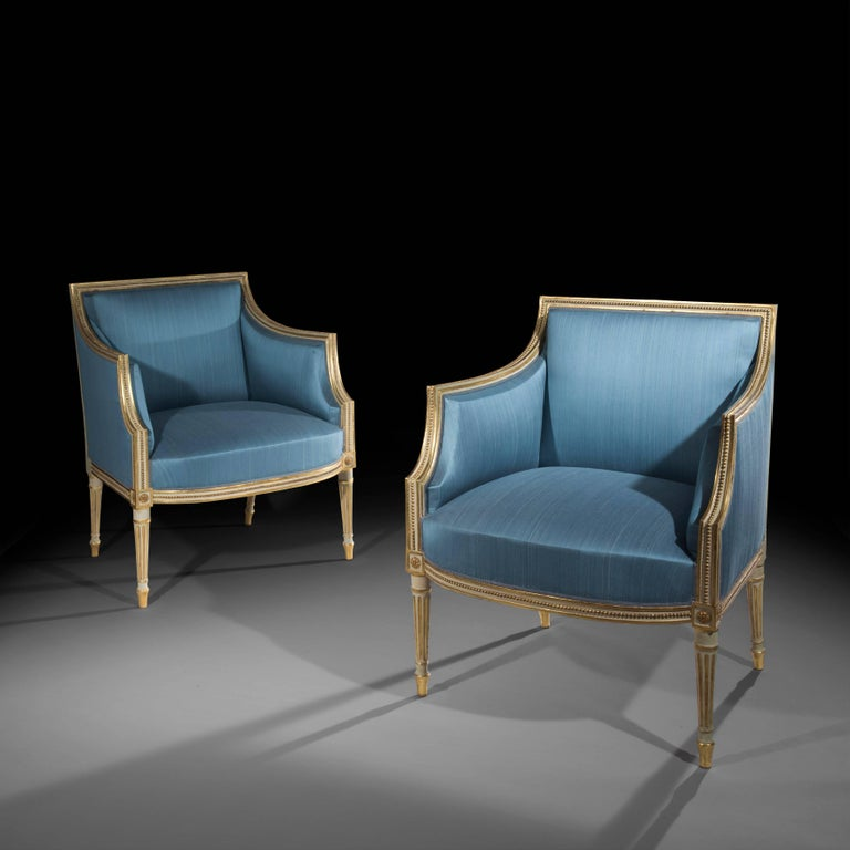 An exceptional pair of George III period cream japanned and parcel-gilt armchairs, having the square backs and sides with bead moulded frames, on turned fluted legs headed by paterae,