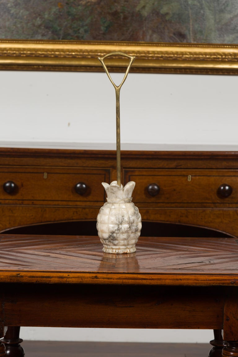 An English doorstop from the mid-20th century, with carved marble pineapple and brass handle. Created in England during the first half of the 20th century, this door porter features a marble pineapple base connected to a brass shaft and handle. A