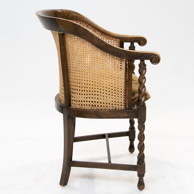English 19th century barrel back armchair This chair is a great accent piece for multiple uses. From England and made of elm and walnut with newly cane seat and back. Luxurious patina and color. This has a comfortable barrel back and a new cushion