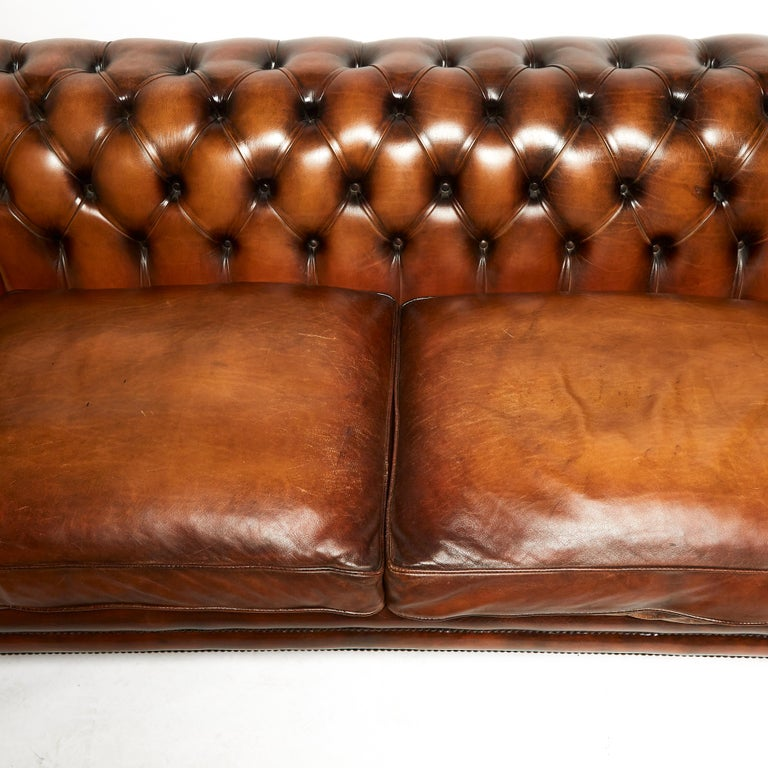 This very good looking and extremely comfortable English chesterfield sofa is made in the traditional 19th century style, standing on front turned and swept back legs. The sofa features 2 separate seat cushions with a generously sized rollback arms