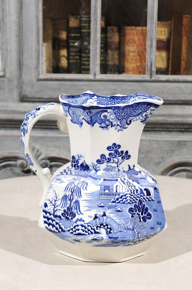 An English blue and white Mason's patent ironstone pitcher from the 19th century, with chinoiserie décor depicting two fishermen on a bridge and willow patterns. Born in England during the 19th century, this exquisite pitcher features an octagonal