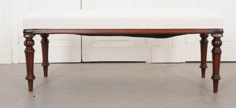 A fantastic George III mahogany bench, circa 1820, from England that features serpentine ends and finely turned legs. Newly upholstered in muslin, this bench is ready for any type of covering.