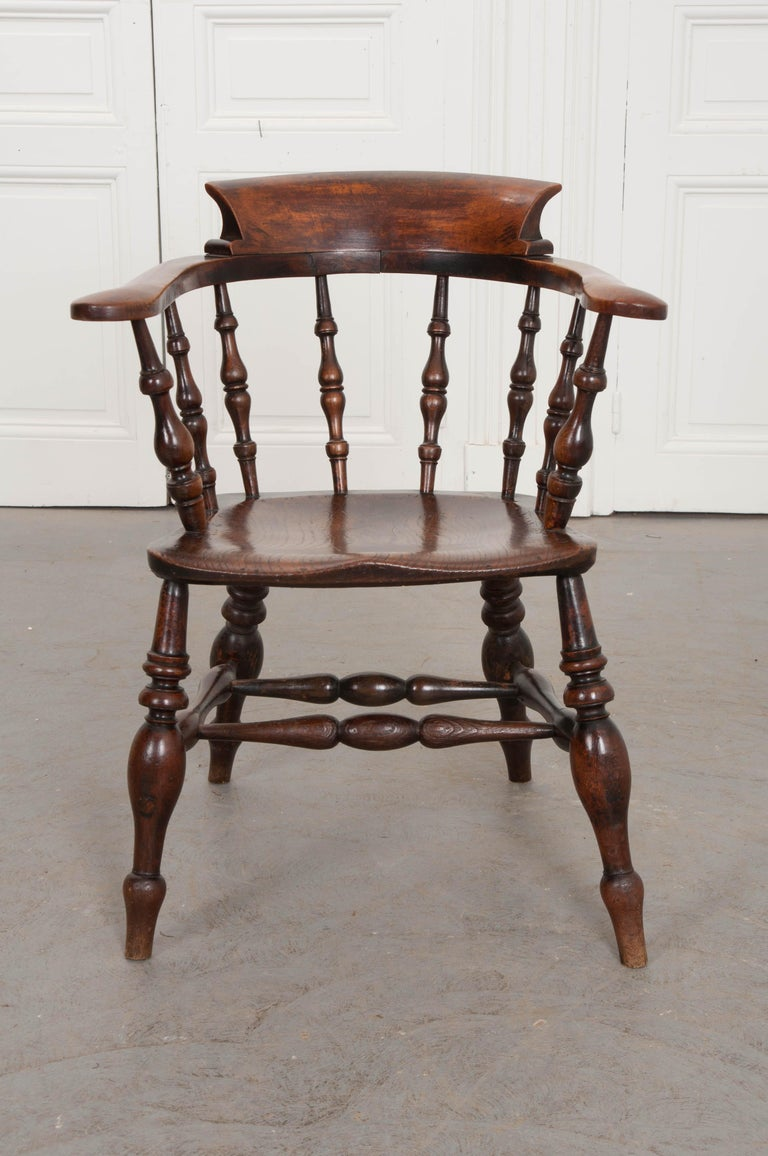 A splendid captain's chair, made in England, circa 1870 of solid oak. The antique has fantastic turned spindle components that join to form a handsome and classically styled chair. The horseshoe shaped armrest, welled seat, and curved top rail have