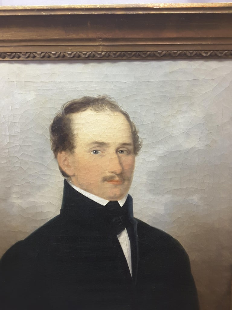 An English 19th century portrait of a gentleman, oil on canvas, original frame and stretcher, crackle paint typical of older paintings of this vintage. There is the remnants of an old gallery label only partial visible due to peeling, also has a
