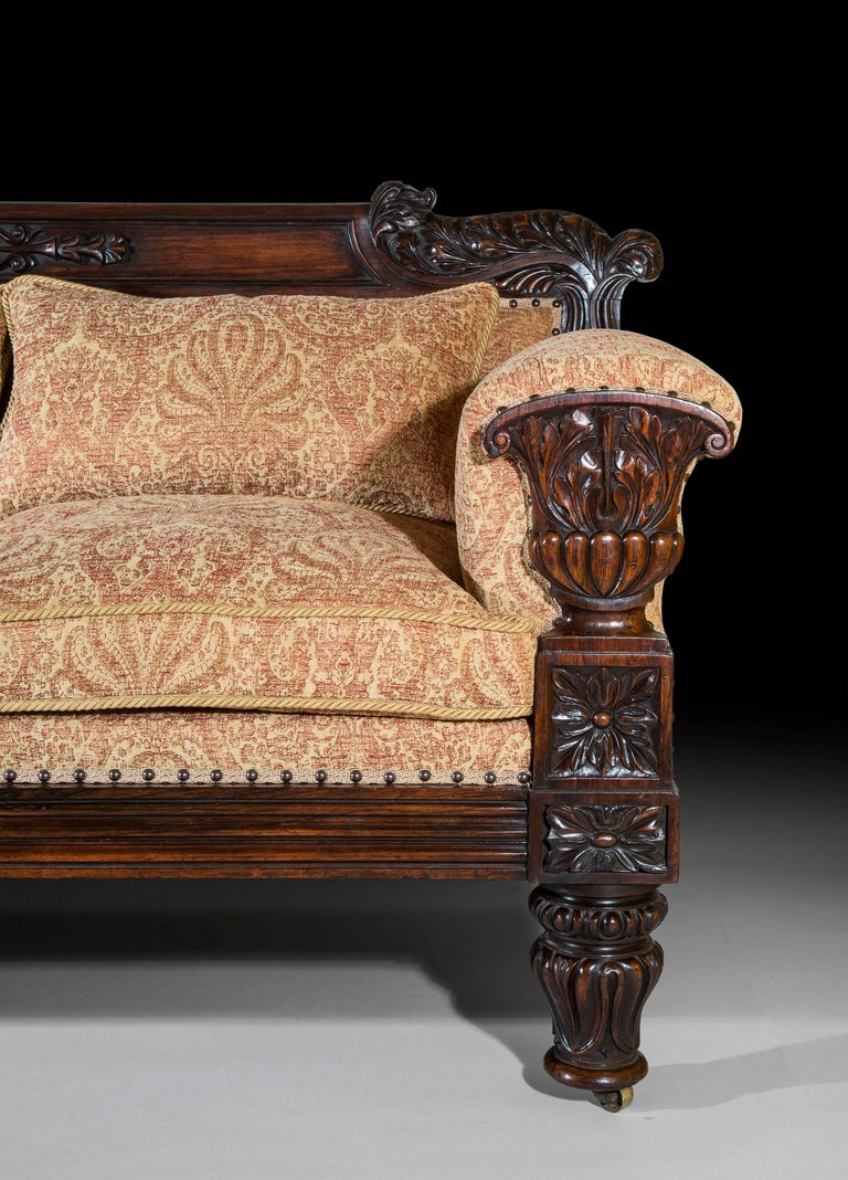 A very fine Regency period sofa in the Grecian taste, after a design by John Taylor, possibly executed by Gillows of Lancaster. English, circa1825.  The panelled toprail centered with floral and foliate trailing carving and flanked