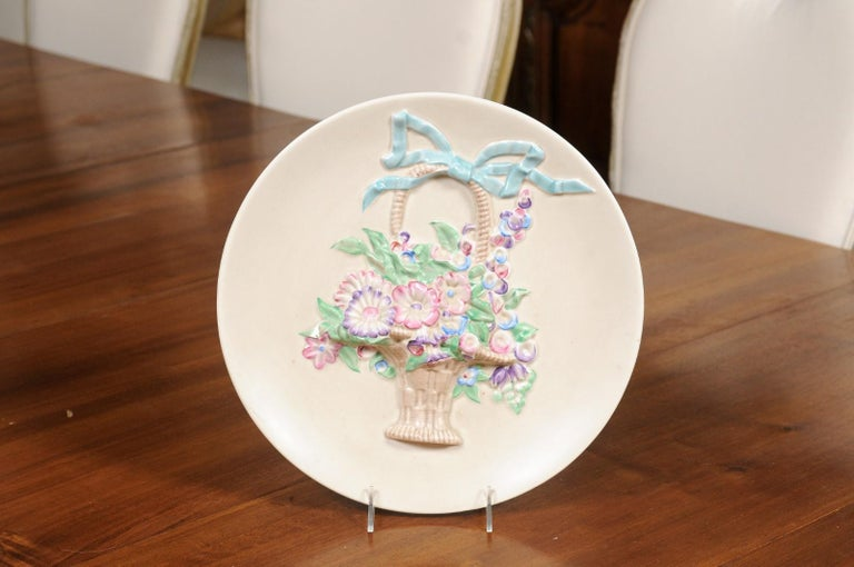 An English porcelain hanging plate from the 19th century, depicting a ribbon tied wicker floral basket and signed Clarice Cliff, Newport Pottery England in the back. Created in England during the 19th century, this porcelain hanging plate, created