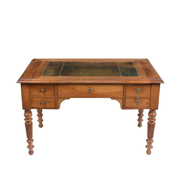 This is beautiful circa 1840s English desk made out of solid walnut wood with its original light walnut color and freshly waxed patina finish. The desktop has its original elegant dark green embossed leather with gilt trim and features four drawers,