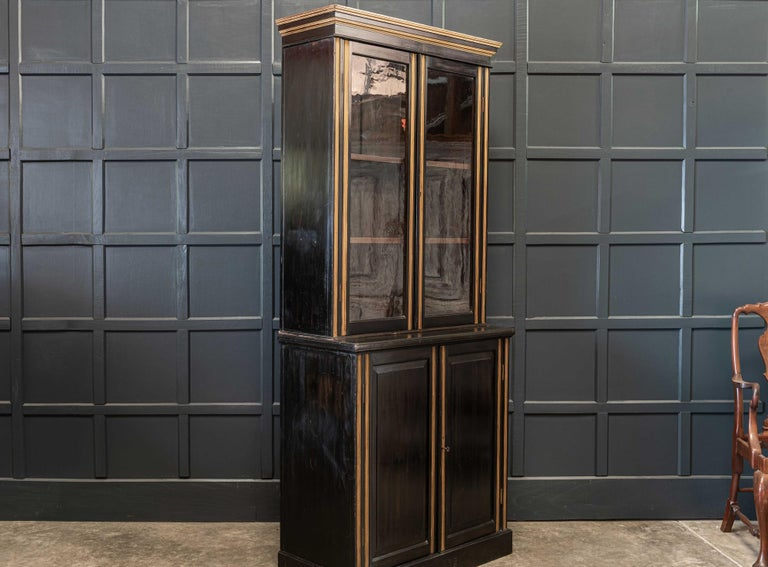 19th century English ebonized glazed bookcase with adjustable cabinet shelving. Original glass, locking key and brass locks. Three sections, great slim proportions,  circa 1850.  Measures: H 220 x W 97.5 x D 45.5cm Cabinet D 31cm.