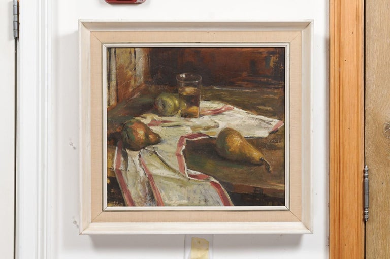 An English oil on canvas still-life painting from the 20th century depicting fruits on a table top and set in a white painted wooden frame. Created in England during the 20th century, this oil on canvas painting depicts three pears and a glass