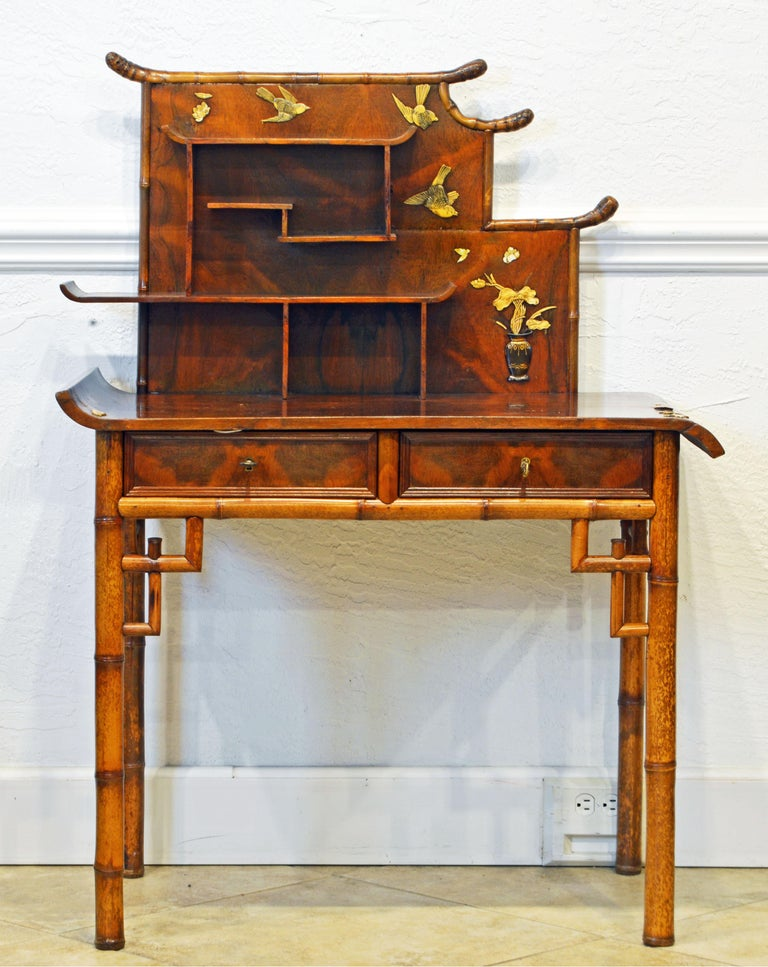 This unique English bamboo and figured walnut secretary desk combines traditional chinoiserie style with the late 19th century's new trends of the Aesthetic movement. The desk top has up swung and down swung ends, the shelves are organized in an