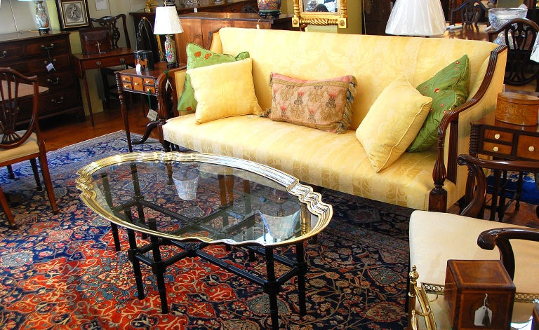 English Art Deco brass and glass coffee table with bamboo turned wooden base. This handsome coffee table has a cast brass undulating stepped edge to a plate glass top. The black lacquered wooden base is turned to look like bamboo, circa 1930.