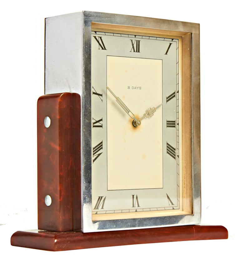 This skyscraper shaped English Art Deco 8-day clock features a totally chrome plated body supported on either side by tortoiseshell/butterscotch Bakelite rounded topped pillars each held in place by by two chrome dome topped bolts and standing on a