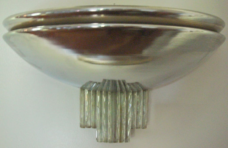 This delightful English Art Deco chrome and glass wall sconce is constructed so that the light will not only shine upwards but horizontally through the gap between its two tiers. The light also shines down through the three uneven blocks of decal