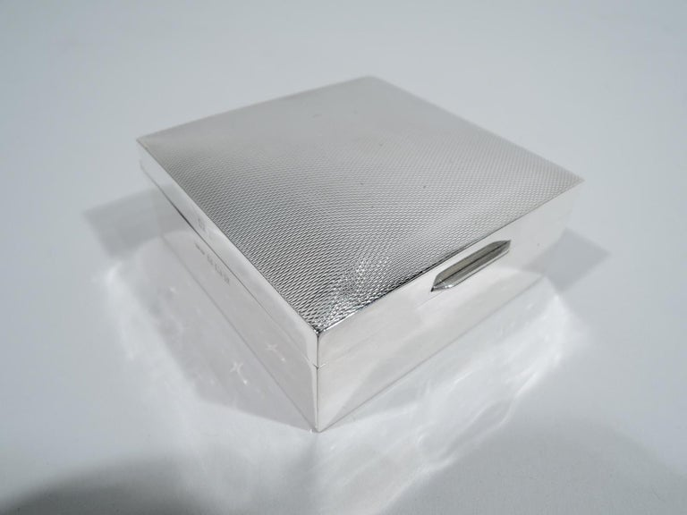English Art Deco sterling silver trinket box, 1956. Square with plain and straight sides. Cover hinged and gently curved with tab and allover engine-turned wave ornament. Box and cover interior cedar lined. Underside inset with laminate. Fully