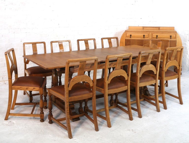 A stylish Art Deco twelve piece oak dining suite dating to the 1930s and comprising a draw leaf dining table, ten chairs and a sideboard. All in solid and veneered golden quarter-sawn oak the dining table is in the refectory style extending by means