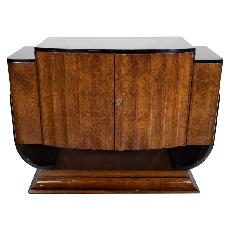 This stunning Art Deco cabinet was realized in the United Kingdom, circa 1930. It features a plinth style concave tiered rectangular base with black lacquer detailing that ascends into two U-form streamlined supports also in black lacquer. The