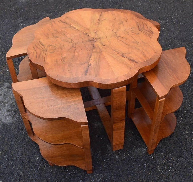 A very stylish 1930's Art Deco nest of tables by Harry & Lou Epstein. The set comprises one large centre table with scalloped edges and four, three tiered triangular inserts with the most exquisite warm walnut veneers. The four pull out side tables