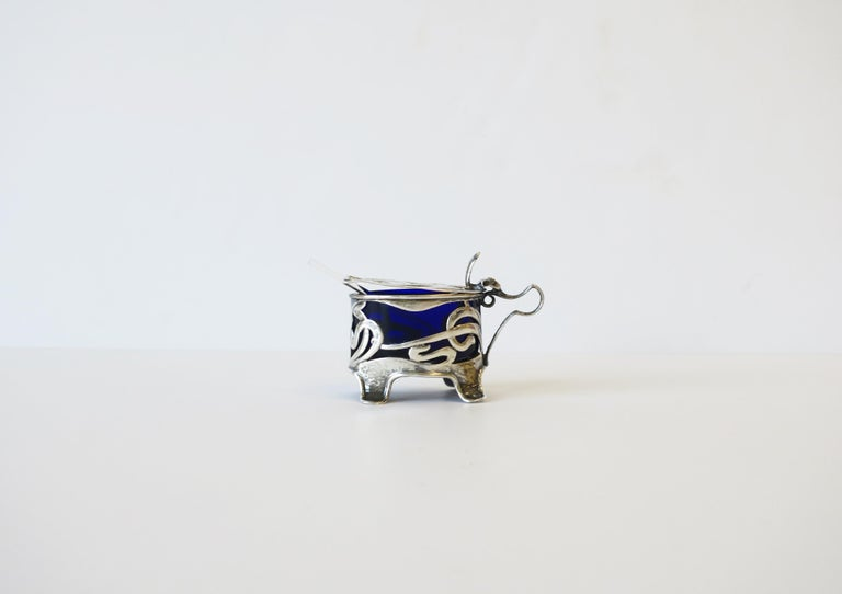 A beautiful English Art Nouveau sterling silver salt (or pepper) cellar, England, circa 20th century. Cellar or vessel has oval sapphire blue glass insert and comes with a small crystal spoon. With marker's and sterling silver mark's shown in image