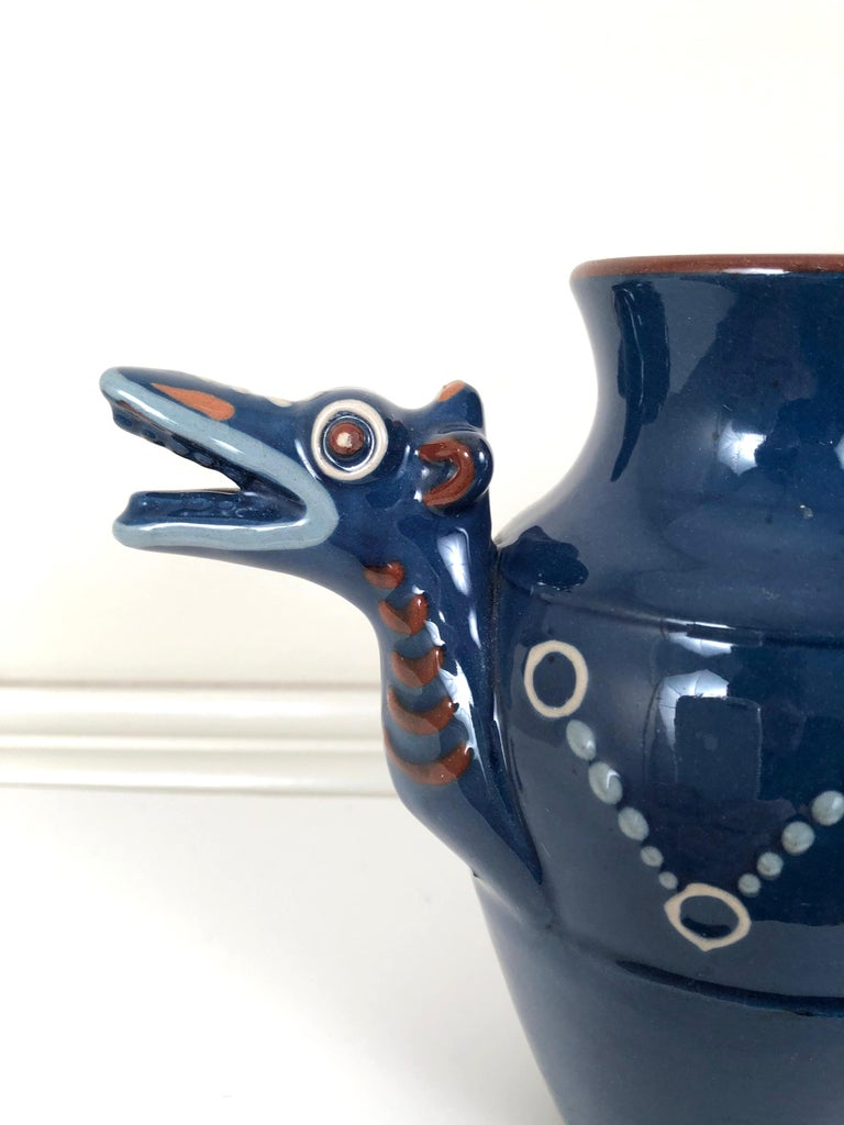 An English Arts & Crafts period pottery Longpark dragon form pitcher, the design attributed to Blanche Vulliamy, its head forming the spout and the curled tail with fins forming the handle, slip decorated with circular motifs in light blue, cream