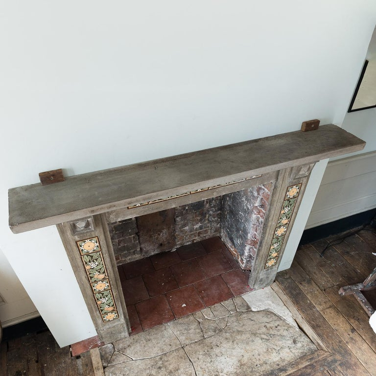 An English Arts & Crafts artificial stone and tiled fireplace, late 19th century, the rectangular shelf supported by stylised Gothic corbels, the frieze and jambs with inset tiles in the manner of May Morris, on plain footblocks.