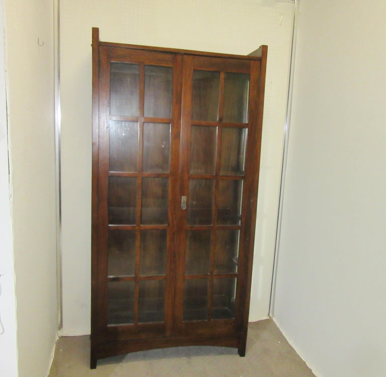English Arts & Crafts mahogany bookcase. The piece has forty individual panes of glass; twenty in the front and ten on each side. There are a total of five wood shelves on the interior for storage. Made in the 1910s in England, the piece is in great