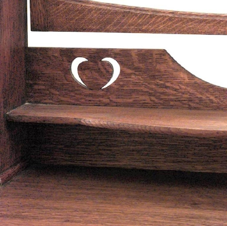 English arts and crafts oak 3 drawer dresser with round wrought iron handles and upper section with bevelled mirror, 2 shelves above small drawers, and cut out design.
