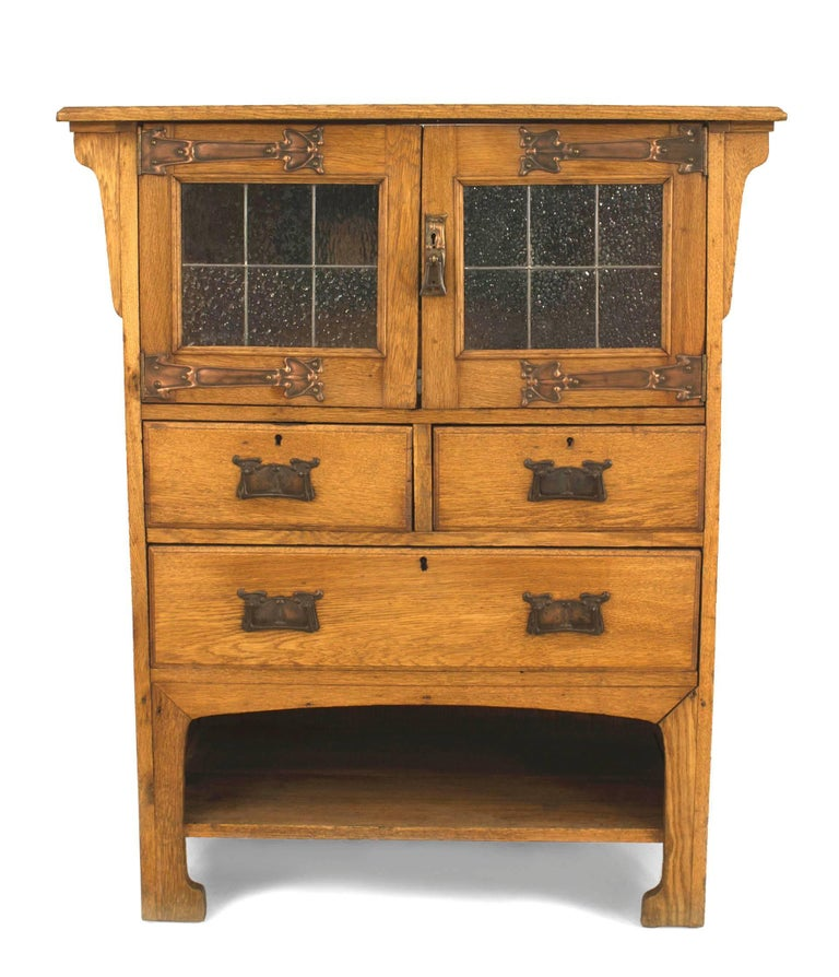 English Arts and Crafts oak cupboard cabinet with copper Art Nouveau hardware and 2 leaded glass doors.
