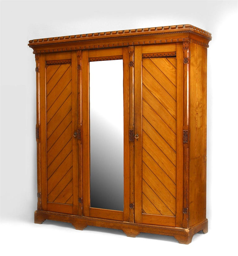 English Arts & Crafts pine armoire cabinet with 2 side doors with slat design centering a mirrored door trimmed with Tudor rose carvings.